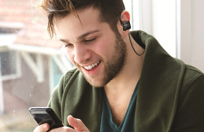Man wearing Jabra Step Wireless looking at phone